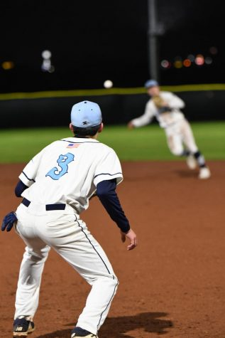 In their second game on the new field, senior shortstop Hunter Wood attempts to throw a Shiloh runner out to senior first baseman Todd Girdner. The Wildcats lost to the Saints 11-1 on March 13.