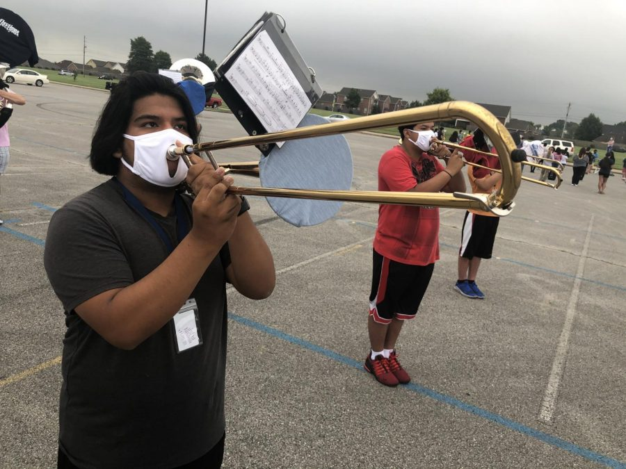 Senior Jose Ortega-Alvarez warms up his trombone in the south parking lot during an early morning practice.